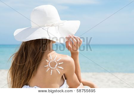 Rear View Of A Young Woman In Bikini And Sun Drawn On Back With Sun Protection Cream