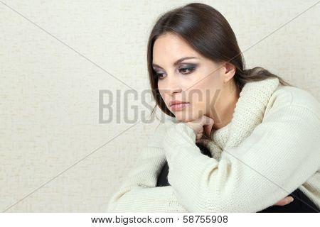 Lonely sad woman near wall