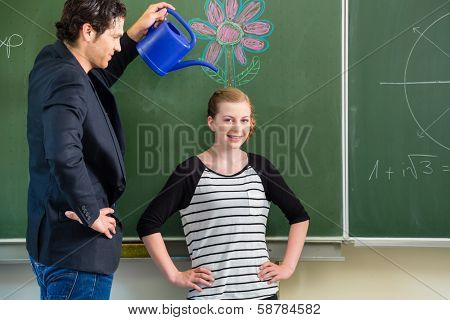 Teacher or docent motivate student or pupil or mate or boy in front of a blackboard or board or chalkboard in a class or school