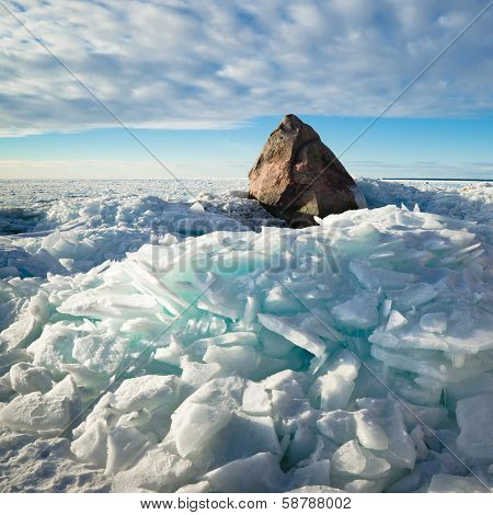 Big stone in the ice on the Baltic Sea coas