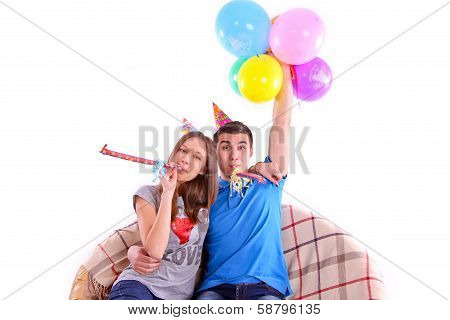 Couple with hats and balloons sitting on the couch isolated