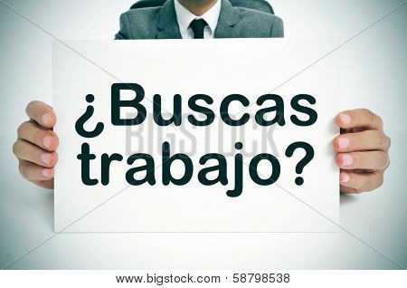a man wearing a suit holding a signboard with the question buscas trabajo? are you looking for a job? written in spanish