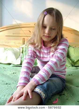 The little girl sitting on the bed