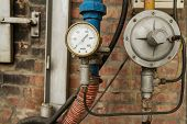 stock photo of air pressure gauge  - Rusty Pressure Gauge connected to pipes with brick wall behind - JPG