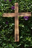 stock photo of crucifiction  - Wooden cross on shrub with purple flowers representing the crusifix - JPG
