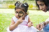 stock photo of peek  - Daughter at outdoor green park with mother - JPG