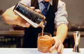 stock photo of liquor bottle  - Bartender is making cocktail at bar counter  - JPG