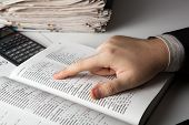 stock photo of glossary  - man is looking for information in the dictionary close - JPG