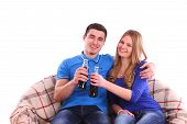 stock photo of coca-cola  - Young couple sitting on a sofa and drinking Coca Cola isolated - JPG