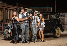 stock photo of tommy-gun  - Group of male and female gangsters with guns - JPG