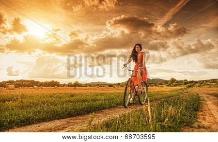 Beautiful woman with old bike in a wheat field