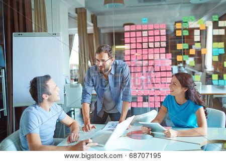 Group of three successful business partners in casual communicating at meeting in office