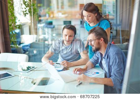 Group of three successful business partners in casual using laptop at meeting in office