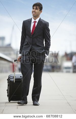 Young Indian businessman with luggage trolley bag on street