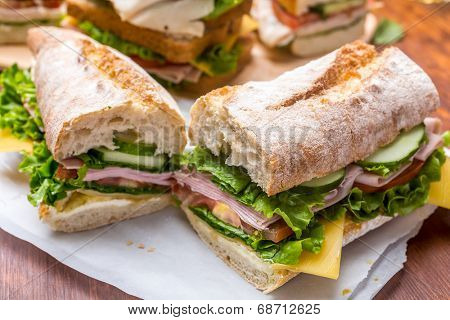 Baguette Sandwich with mustard, lettuce, slices of fresh tomatoes, ham, and cheese cut in half