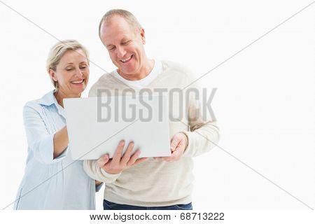 Happy mature couple using laptop on white background
