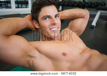Smiling young muscular man doing abdominal crunches in gym