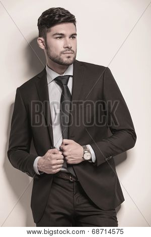 young business man holding his collar and looks away from the camera
