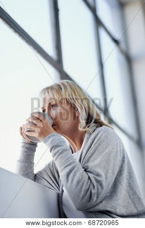 Beautiful blonde woman sipping a cup of tea while looking out the window