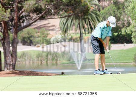 Male teen golfer preparing to putt