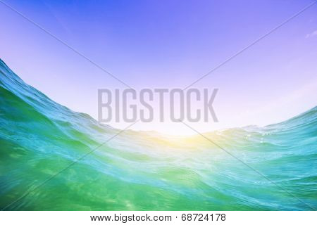 Dynamic water wave in the ocean. View from the waterline. Underwater and blue sunny sky.