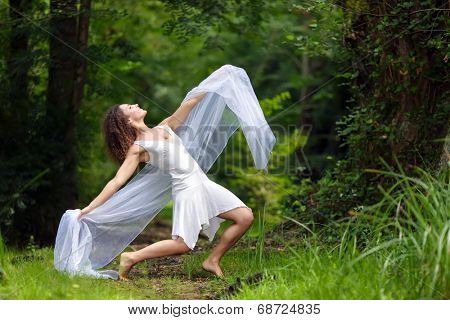 Artistic portrait of a beautiful barefoot woman in a stylish white dress striking a dramatic pose with her outstretched arms draped in filmy white chiffon against a forest backdrop of lush green trees