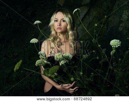 Twilight portrait of beautiful young lady with bouquet of flowers