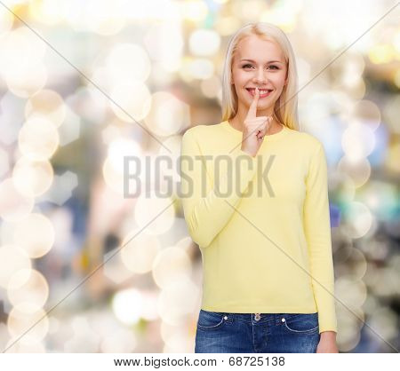 advertisement concept - attractive young woman with finger on her lip