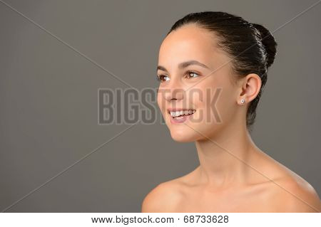 Teenage girl bare shoulders skin cosmetics beauty smiling on gray background