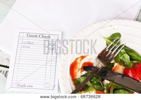 Check and remnants of salad on table in restaurant