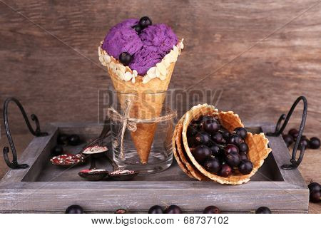Tasty ice cream with berries in waffle cone on brown wooden background
