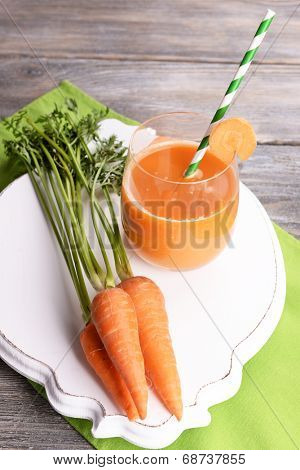 Glass of carrot juice and fresh carrots on wooden table