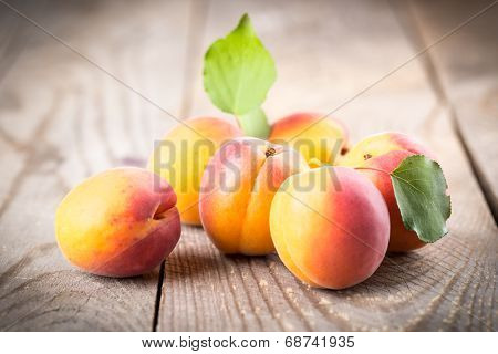Apricot with leaves on a wooden background