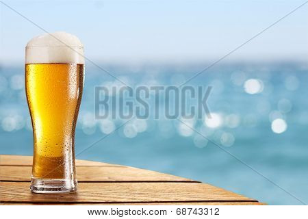 Beer glass on a blurred background of the sea.