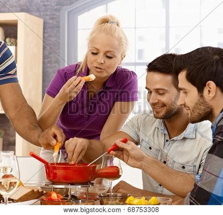 Young friends having cheese fondue at home.