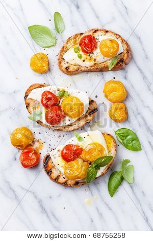 Bruschetta With Roasted Tomatoes And Mozzarella Cheese On Grilled Crusty Bread On White Marble