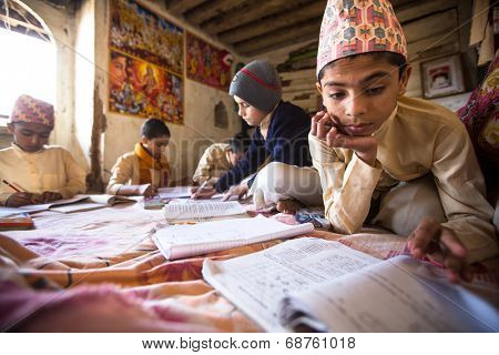 KATHMANDU, NEPAL - DEC 9, 2013: Unknown children doing homework at Jagadguru School. School established at 2013, to let new generation learn Sanskrit and preserve Hindu culture.