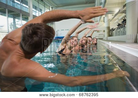 Female fitness class doing aqua aerobics with male instructor in swimming pool at the leisure centre