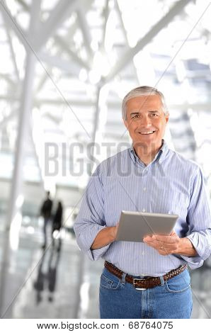 A mature businessman in the lobby of a modern office building. The casually dressed man is smiling and there are blurred people in the background.