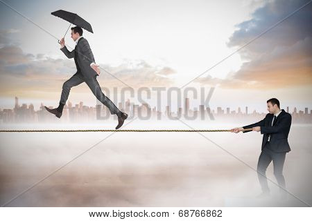 Young businessman pulling a tightrope for business man against cityscape on the horizon