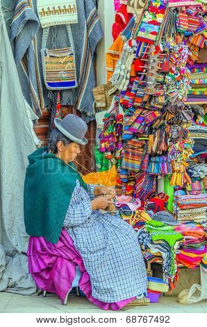 LA PAZ, BOLIVIA, MAY 9, 2014 - Local woman in traditional costume and bowler hat sits in front of her souvenir stand, knitting