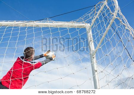 Goalkeeper in red making a save on a clear day