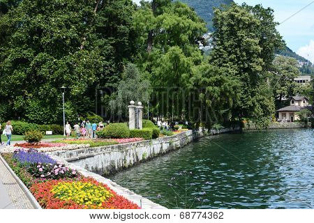 LUGANO, SWITZERLAND - JULY 5, 2014: People stroll along the shoreline in the Parco Ciani. The area has English-style gardens, flowerbeds and grass areas with trees and plants from all over the world.