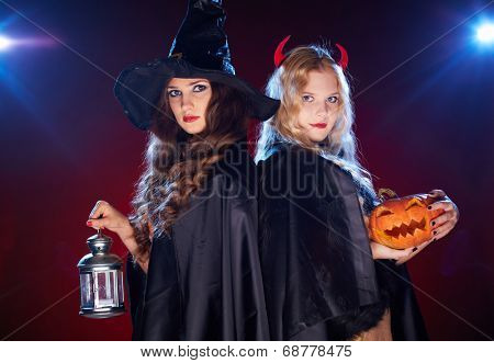 Portrait of two females with lantern and pumpkin looking at camera in the dark