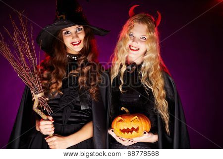 Portrait of two happy females with broom and pumpkin looking at camera with smiles