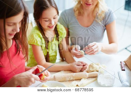 Two girls and their mother cooking pastry in the kitchen