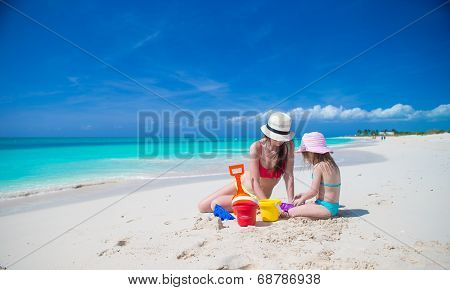 Little cute girl and young mother building sandcastle at tropical beach