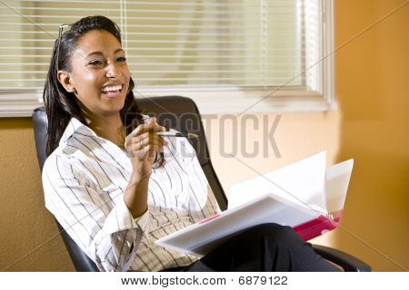 Young African-American woman in office taking notes