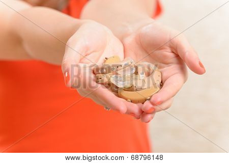 Woman showing deaf aids on her hands