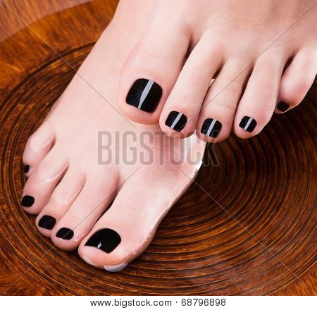 Beautiful women legs with black pedicure after Spa procedures - Spa treatment concept